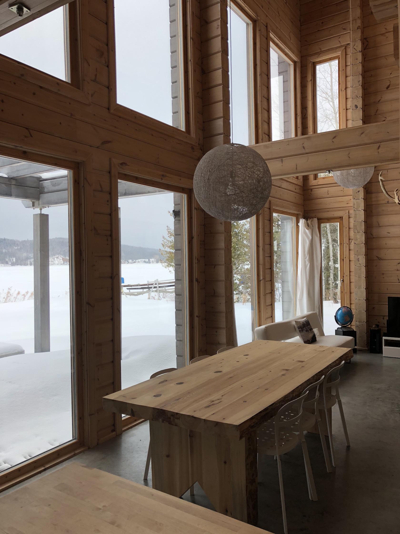 La salle à manger avec fenêtres abondantes sur le lac au Chalet les Hirondelles